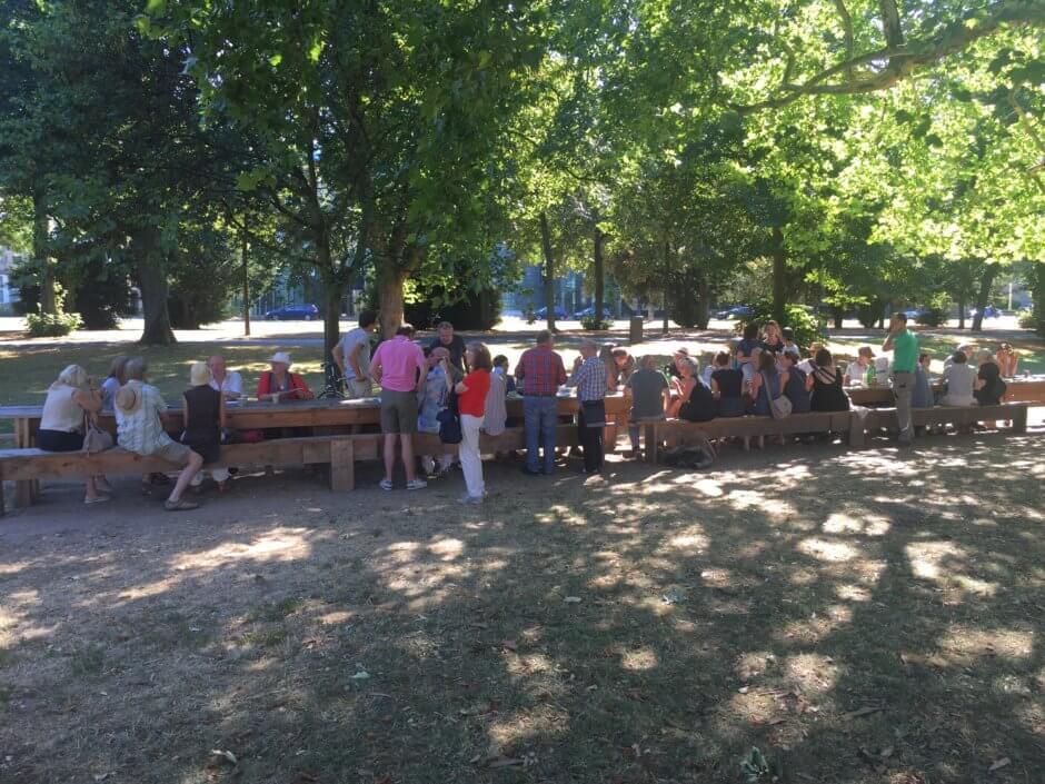 Langer Tisch im kleinen Park Sachsenring vor dem Humboldt; Menschen am Tisch